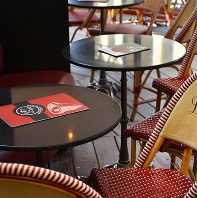 A l'extérieur, la grande terrasse vous accueille confortablement sous ses parasols rouges été comme hiver